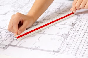 Two hands using a scale ruler on a set of blueprints